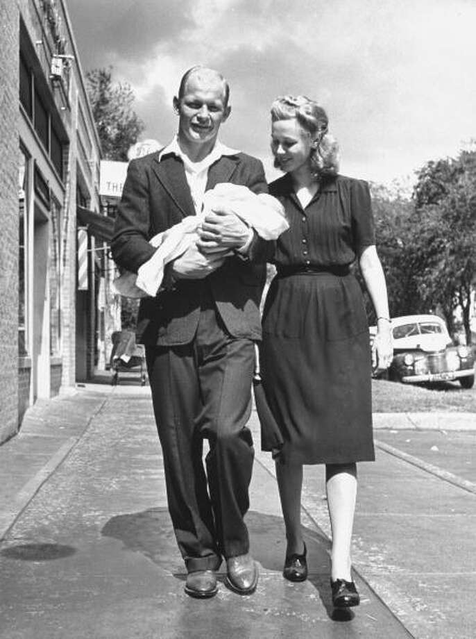 Circa 1940s - Football player Jack Freeman of the Univ. of Texas walking down sidewalk with wife and baby.  (Photo by George Strock//Time Life Pictures/Getty Images) Photo: George Strock, Time & Life Pictures/Getty Image / Time Life Pictures