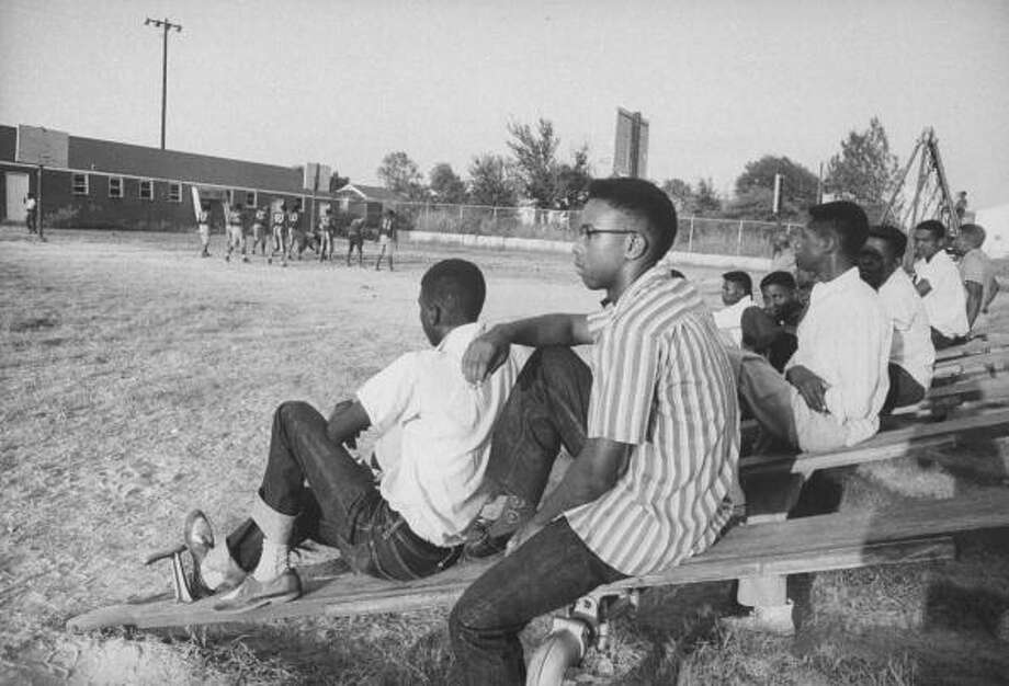 Circa 1950s - Student Steve poster (foreground), who along with another student Jessalyn Gray were blocked from entering Texarkana College by group of White Supremacists, watching High School football practice.  (Photo by Joseph Scherschel//Time Life Pictures/Getty Images) Photo: Joseph Scherschel, Time & Life Pictures/Getty Image / Time Life Pictures
