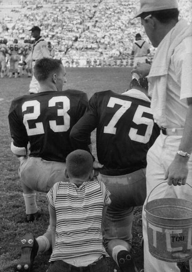 A younger fan watches two older players during a Texas football game in the 1950s. (Photo by Joseph Scherschel/Time & Life Pictures/Getty Images) Photo: Joseph Scherschel, Time Life Pictures/Getty Images / Time & Life Pictures