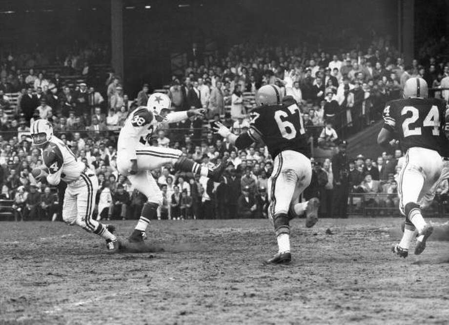 Eddie LeBaron #14 of the Dallas Cowboys rolls out on a fake punt executed by Sam Baker #38 against Bob Schmitz #67 and Johnny Sample #24 of the Pittsburgh Steelers during the game at Pitt Stadium on October 21, 1962 in Pittsburgh, Pennsylvania. (Photo by Robert Riger/Getty Images) Photo: Robert Riger, Getty Images / 1962 Robert Riger