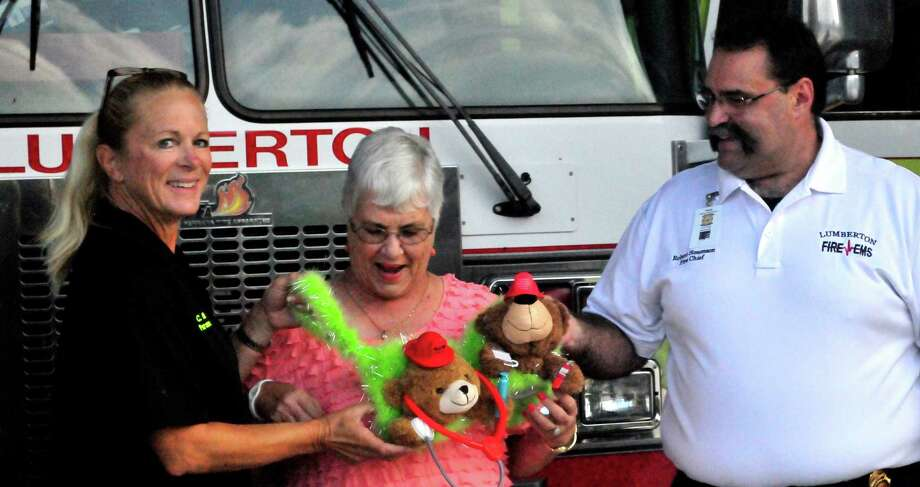 Paramedic Christy Bonin, breast cancer survivor Shirley Johnson and Lumberton Fire Chief Robert Simonson on Sept. 4 hold a decorated bra the department donated on Johnson s behalf to the Julie Rogers Gift of Life Bravo Applause for the Cause. Johnson, Fire Department Auxiliary President, has been cancer free since 2007 after having a double mastectomy. Johnson feels strongly about supporting breast cancer research because she s lost a sister to breast cancer, another sister and her niece had breast cancer and her son and daughter both had thyroid cancer. Photo: Cassie Smith