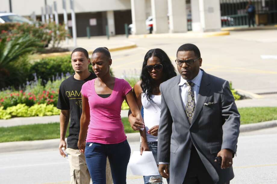Family members of a victim in a Wednesday morning stabbing at Spring High School walk with Pastor E.A. Deckard as they cross the street to answer questions about the victim. Photo: Cody Duty, Chronicle