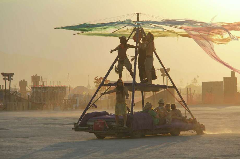 "An art car on the move with a Burner giving his best ""I'm king of the world"" impression at Burning Man 2013. http://www.fest300.com/ Photo: Art Gimbel / Fest300.com"