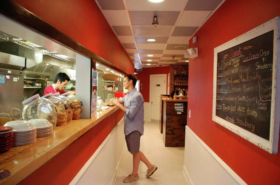 Andrew Ugenti of New Jersey, who works in Darien, right, has his first look at Meatball & Co., 20 Center St., Darien, helped by Maxwell Kim at the counter. Jarret Liotta/For the Darien News Photo: Contributed
