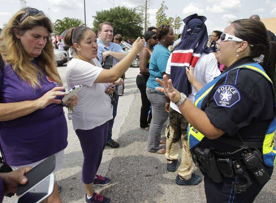 A Spring ISD police officer talks to parents outside Spring High School where a student was fatally stabbed and three others injured Wednesday, Sept. 3, 2013.  (Melissa Phillip/ Houston Chronicle) Photo: Melissa Phillip, Houston Chronicle