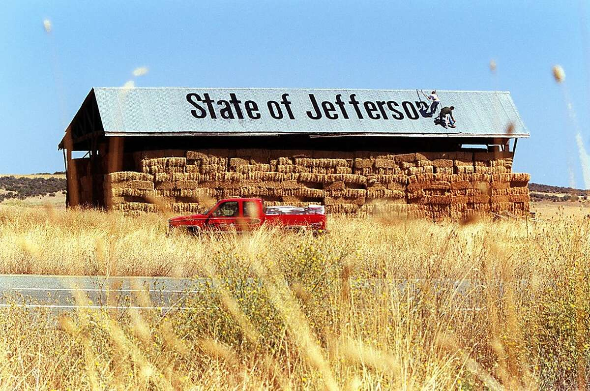 SISKIYOU13/C/26SEP98/SC/CS - Brian Helsaple (dark shirt) and his nephew Ross Helsaple, 18, paint a protest sign on a hay barn along Highway 5 south of Yreka in Siskiyou county. Mt. Shasta looms in the background at right. The sign reads