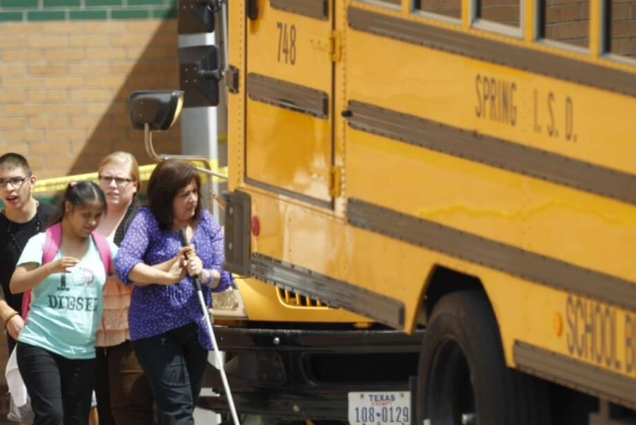 Students are being loaded onto buses outside Spring High School where a student was fatally stabbed and three others injured Wednesday, Sept. 3, 2013. Photo: Brett Coomer, Chronicle