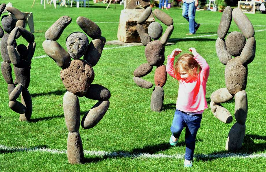 Avery Slaughter, 2, of Bethel, imitates a stone sculpture at the Newtown Arts Festival Saturday, Sept. 15, 2012. Photo: Michael Duffy / The News-Times