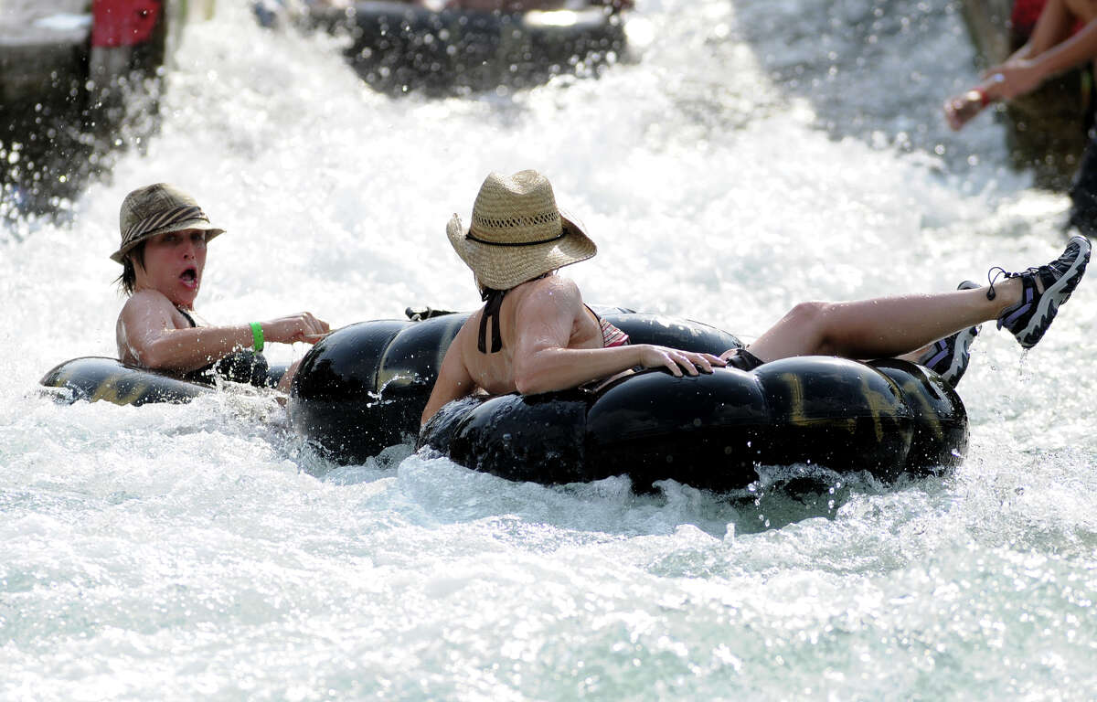 """Natalie Jobe, left, and Kelly Ketter, both from Austin, rush through the City Tube Chute on the Comal River in New Braunfels on Friday. Despite less than average rainfall for several years and an increase in water consumption, water levels on the Comal River near New Braunfels have only dropped slightly over the past year. """"Maybe a foot or so in some spots,"""" said John Driscoll, a lifeguard on the river. Although the water level has dropped, people still flock to the popular destination in Comal County. """"It's steady all week and then packed on the weekends,"""" Discoll continued. Patrick Meredith for HOUSTON CHRONICLE 7/30/09"""