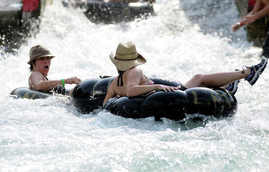 """Natalie Jobe, left, and Kelly Ketter, both from Austin, rush through the City Tube Chute on the Comal River in New Braunfels on Friday.  Despite less than average rainfall for several years and an increase in water consumption, water levels on the Comal River near New Braunfels have only dropped slightly over the past year.  """"Maybe a foot or so in some spots,"""" said John Driscoll, a lifeguard on the river.  Although the water level has dropped, people still flock to the popular destination in Comal County.  """"It's steady all week and then packed on the weekends,"""" Discoll continued.  Patrick Meredith for HOUSTON CHRONICLE 7/30/09 Photo: Patrick Meredith, Freelance / Freelance"""