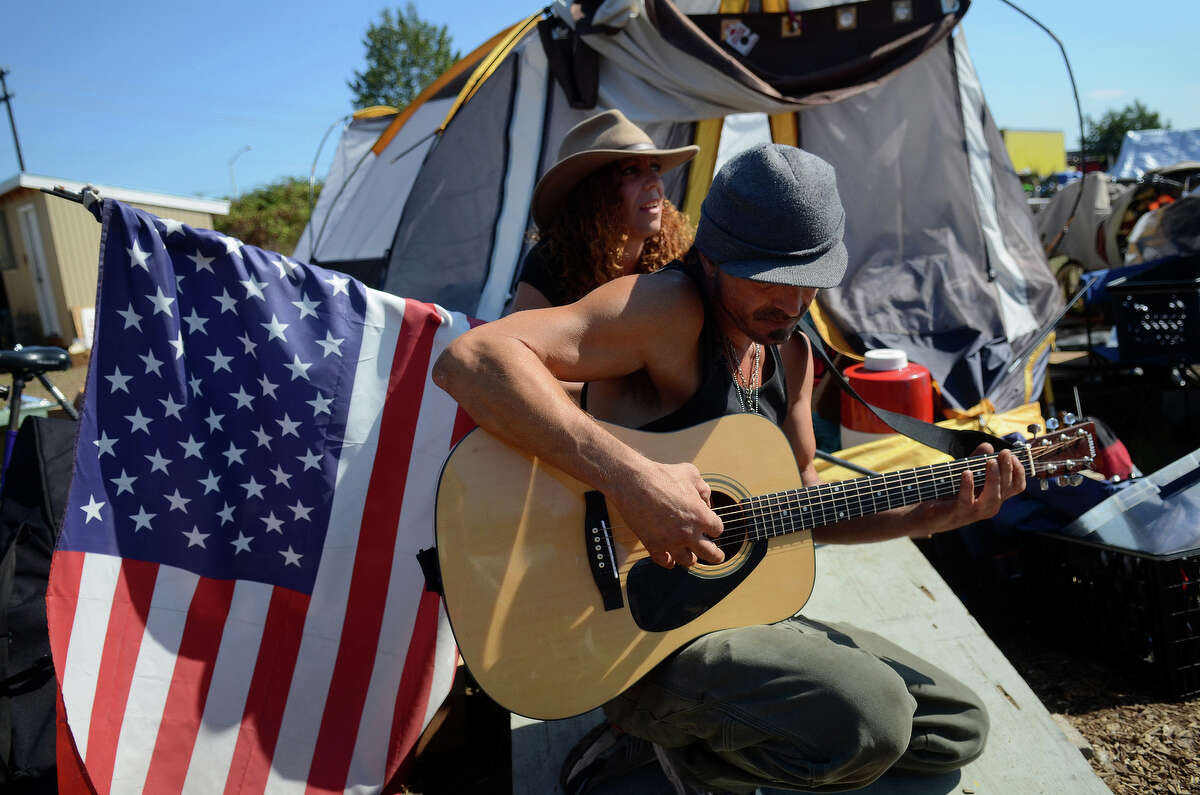 Penny Lane Pannek, behind, and Dale Hickman, play music as residents of the Nickelsville homeless campsite get evicted Sunday, Sept 1, 2013 in West Seattle. Pannek has lived at the campsite for 2 months.