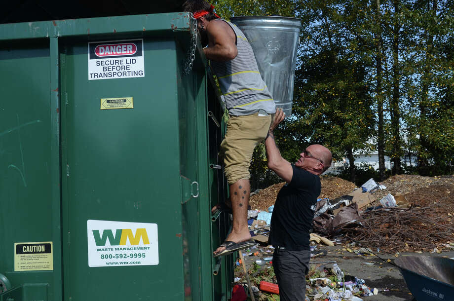 Michael Holmes throws garabage into a dumpster during the eviction of the Nickelsville camp Sunday, Sept. 1, 2013 in West Seattle. Holmes has been living at the site for 6 months, and is uncertain where he will move next. Photo: SY BEAN, SEATTLEPI.COM / SEATTLEPI.COM