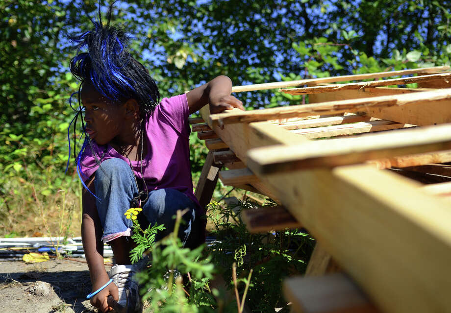 Joselynn Smith, 8, plays on pallets as her family is evicted from the Nickelsville homeless camp on Sunday, Sept 1, 2013 in West Seattle. Photo: SY BEAN, SEATTLEPI.COM / SEATTLEPI.COM