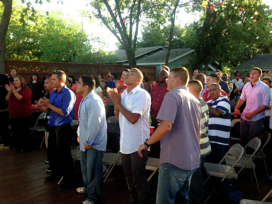 Inductees to the Outcry in the Barrio Leadership Academy sing and pray during an orientation and barbecue dinner at the home of the Outcry in the Barrio's pastor, Jubal Garcia. Photo: Sarah Tressler / Express-News