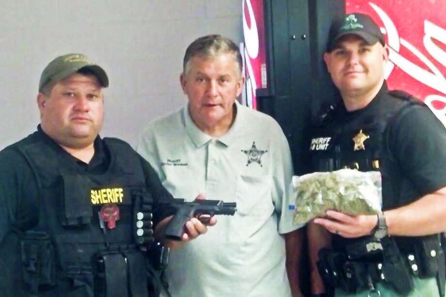 Narcotics Lts. S. Jacks and S. Duncan, along with Sheriff Newman, exhibit confiscated contraband from recent drug bust at America's Best Value Inn in Jasper.