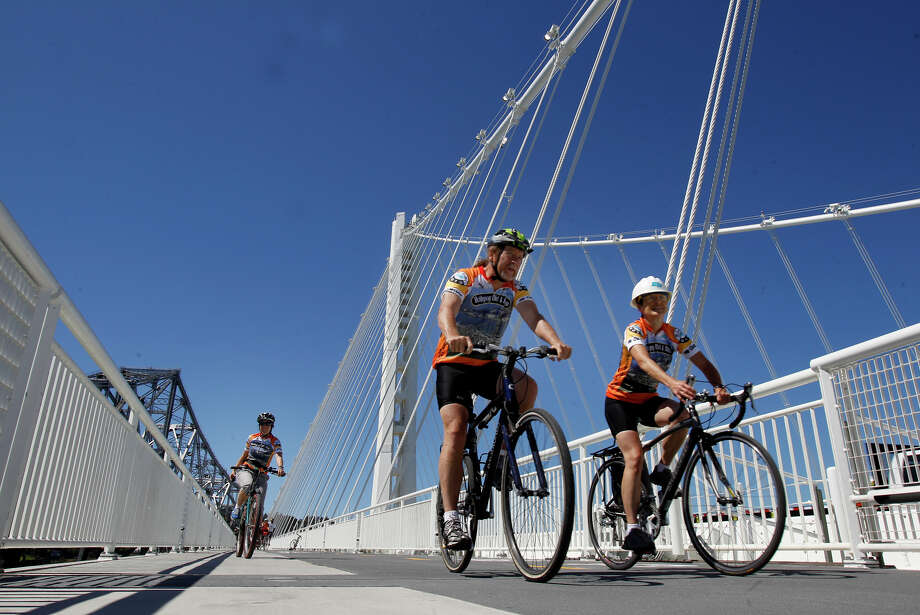Cyclists ride by the Bay Bridge eastern span's tower on the Alexander Zuckermann bicycle and pedestrian path on its first day of operation, Sept. 3, 2013. Transit officials are exploring the option of creating a bike path that spans the entire bridge, from Oakland to San Francisco. Photo: Brant Ward / The Chronicle / ONLINE_YES