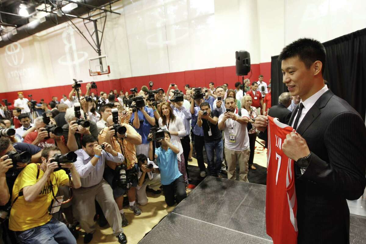 Jeremy Lin poses with his jersey for media members during his introductory news conference.