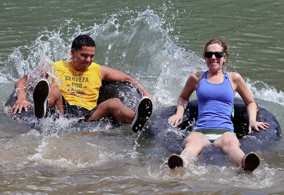 Andrew Guevara and Ashley Moore splash into the stream as tubers float in the Guadalupe River near Sattler  on September 2, 2013. Photo: TOM REEL