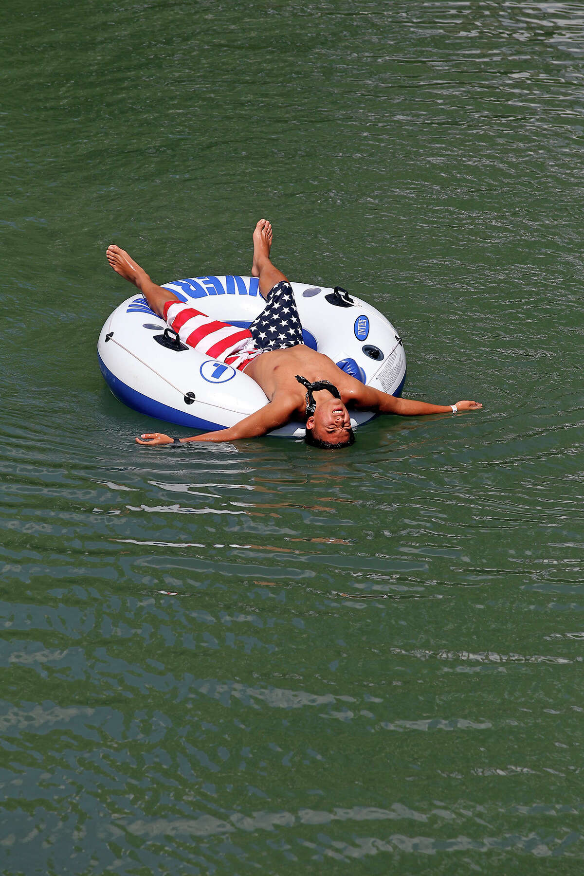 Anthony Gomez leans back into the water to cool off as tubers float in the Guadalupe River near Sattler on September 2, 2013.