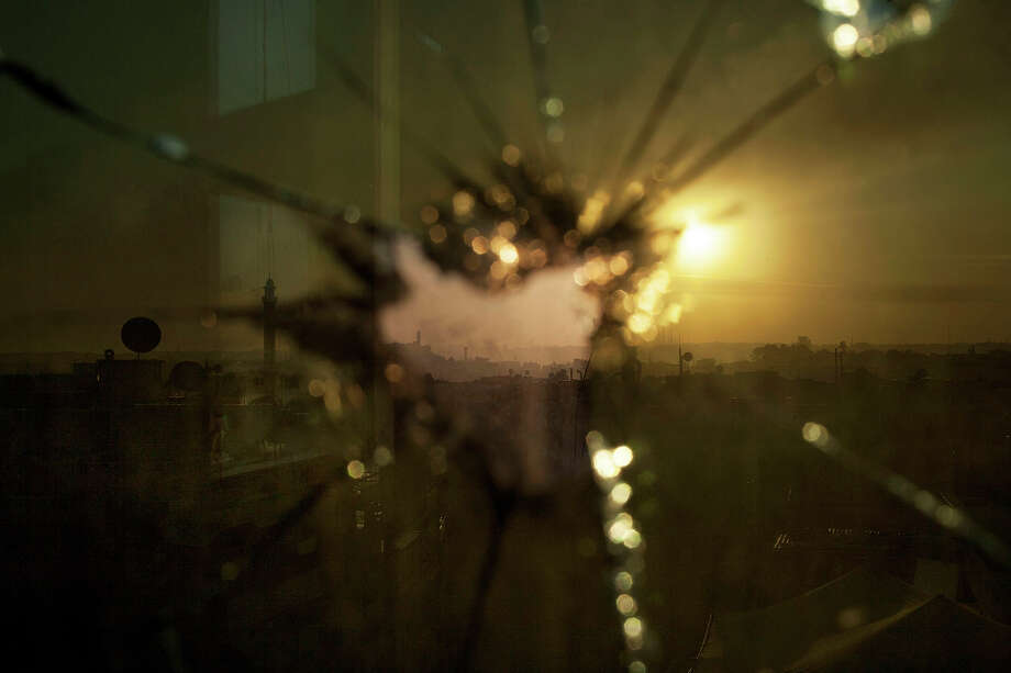 In this Saturday, Oct. 13, 2012 photo, smoke rises from buildings due to government forces shelling seen through broken glass in Aleppo, Syria. Photo: Manu Brabo, ASSOCIATED PRESS / AP2012