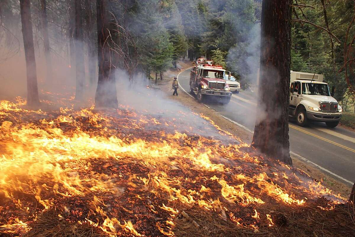 In this photo provided by the U.S. Forest Service, fire crew members stand watch near a burn area as they fight the Rim Fire near Yosemite National Park in California Sunday, Sept. 1, 2013. The massive wildfire is now 75 percent contained according to a state fire spokesman. (AP Photo/U.S. Forest Service, Mike McMillan)