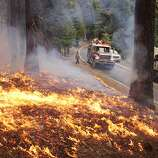 In this photo provided by the U.S. Forest Service, fire crew members stand watch near a burn area as they fight the Rim Fire near Yosemite National Park in California Sunday, Sept. 1, 2013. The massive wildfire is now 75 percent contained according to a state fire spokesman.