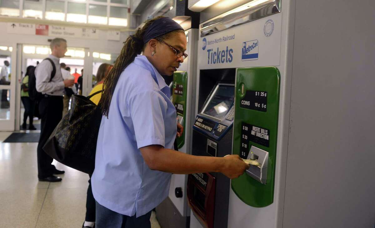 Cynthia Clarke, of Bridgeport, who was injured in the train crash in May, buys her train ticket at the Bridgeport transit station Wednesday morning Sept. 4, 2013 on her first day back to work following the crash. Clarke is a Postal Letter Carrier in Norwalk.