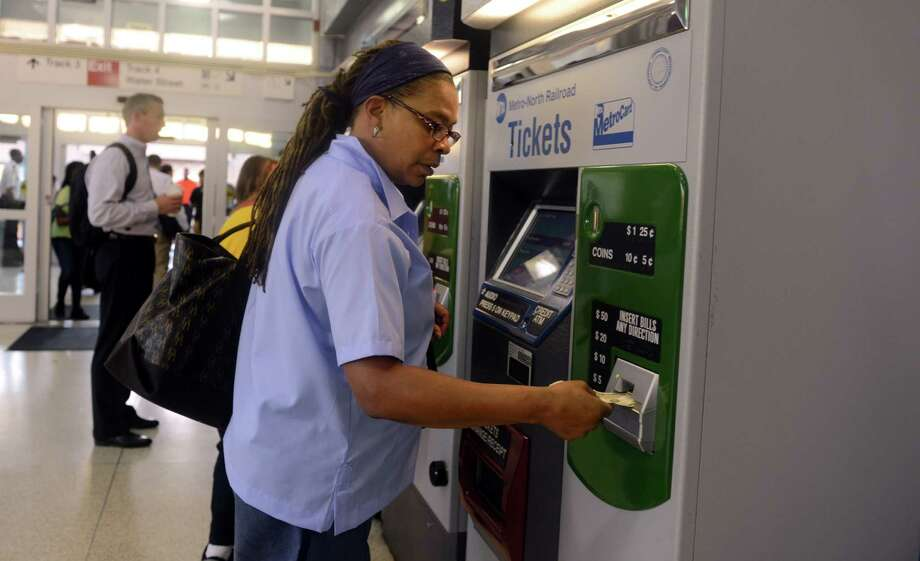 Cynthia Clarke, of Bridgeport, who was injured in the train crash in May, buys her train ticket at the Bridgeport transit station Wednesday morning Sept. 4, 2013 on her first day back to work following the crash. Clarke is a Postal Letter Carrier in Norwalk. Photo: Autumn Driscoll / Connecticut Post