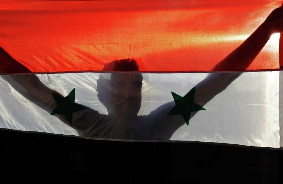 In a refugee camp, a Palestinian supporter of the Popular Front for the Liberation of Palestine holds a Syrian flag during a protest against a possible military attack by the United States on Syria. Photo: Adel Hana / Associated Press