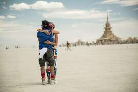 "Two Burning Man participants embrace during the 2012 event in, ""Spark: A Burning Man Story."""