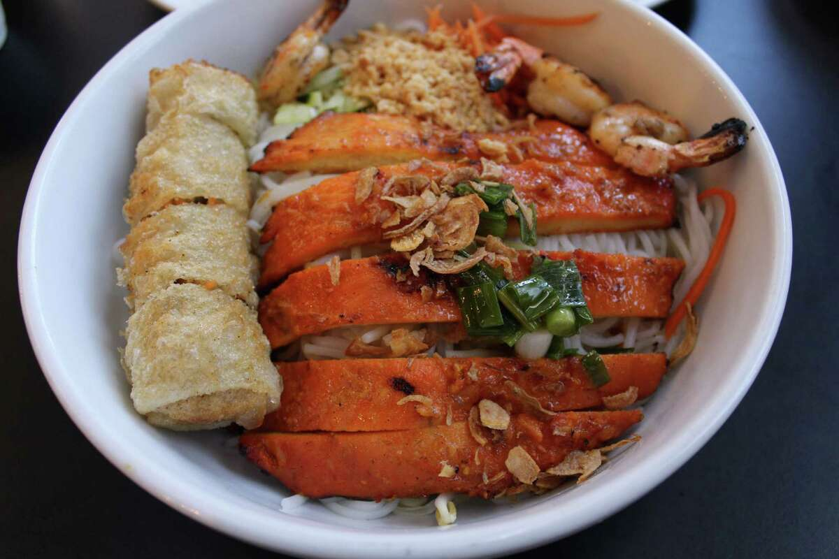 Bun, or vermicelli bowls, are topped with different items. This one features chicken, shrimp and cha gio, also known as a Vietnamese egg roll or fried spring roll.