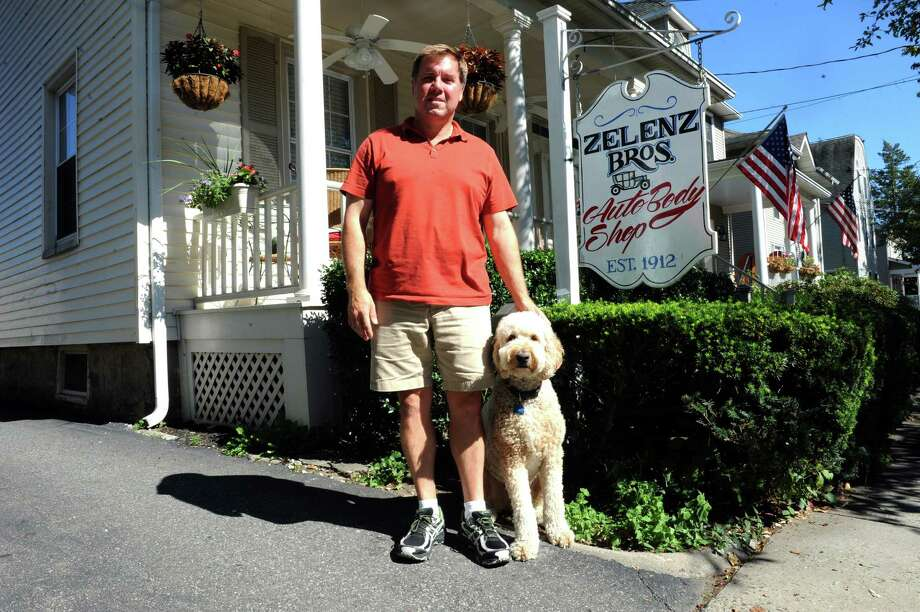 Mike Zelenz, of Zelenz Autobody Shop, with his dog Terrence, is glad his stolen business sign was returned anonymously last week with a lengthy note, Greenwich, Conn., Wednesday, Sept., 4, 2013. Photo: Helen Neafsey / Greenwich Time