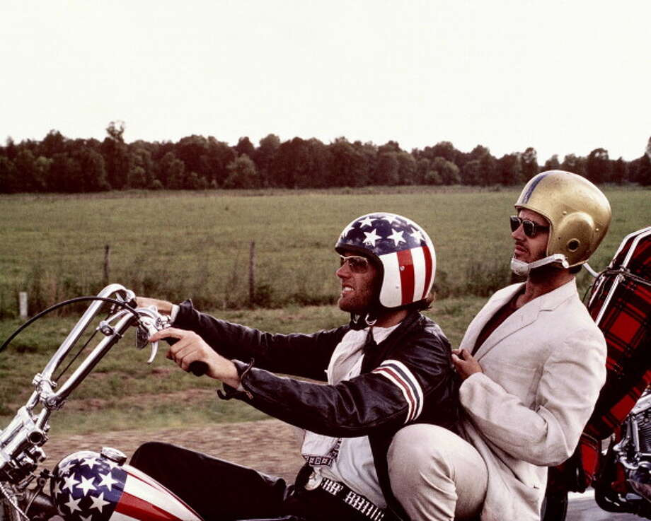 Peter Fonda, wearng a stars-and-stripes helmet, and Jack Nicholson, wearing a gold American football helmet, as they ride Fonda's chopper motorcycle in a publicity still issued for the film, 'Easy Rider', USA, 1969. The film, directed by Dennis Hopper, starred Fonda as 'Wyatt', and Nicholson as 'George Hanson'. (Photo by Silver Screen Collection/Getty Images) Photo: Silver Screen Collection, Getty Images / 2011 Silver Screen Collection