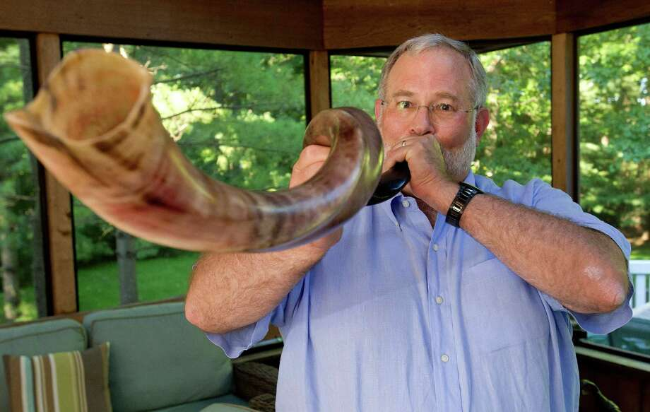 Michael Stone practices blowing the shofar in his Stamford home on Wednesday, September 4, 2013. Stone will blow the shofar at Temple Sini for Rosh Hashana. Photo: Lindsay Perry / Stamford Advocate