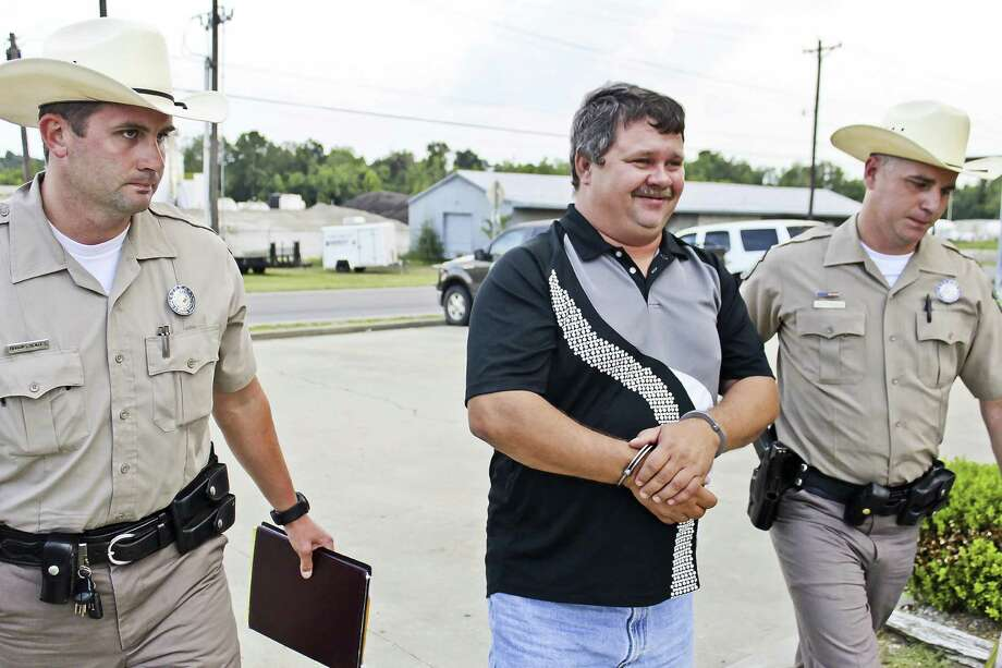 Michael McCloud Jr.,  tournament director of Big Bass Mania, being escorted in to Jasper County Jail on Tuesday, Sept. 3, 2013 by Texas Parks and Wildlife Game Wardens Ellis Powell and Brooks Yeates  Photo by Alison Hart.