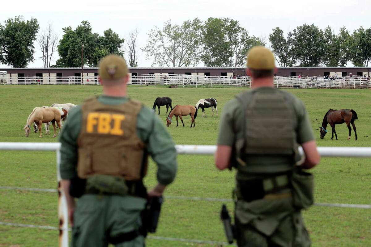 FILE - In this June 12, 2012 file photo, FBI agents overlook a horse ranch under investigation in Lexington, Okla. Prosecutors in Texas say Jose Trevino Morales, a brother of two top leaders of Los Zetas, oversaw the purchase of hundreds of quarter horses at a ranch in Oklahoma. He's charged with conspiracy to launder drug money in a case with more than a dozen other defendants. Jury selection in the trial begins Monday, April 15, 2013, in Austin, Texas. (AP Photo/Brett Deering, File)