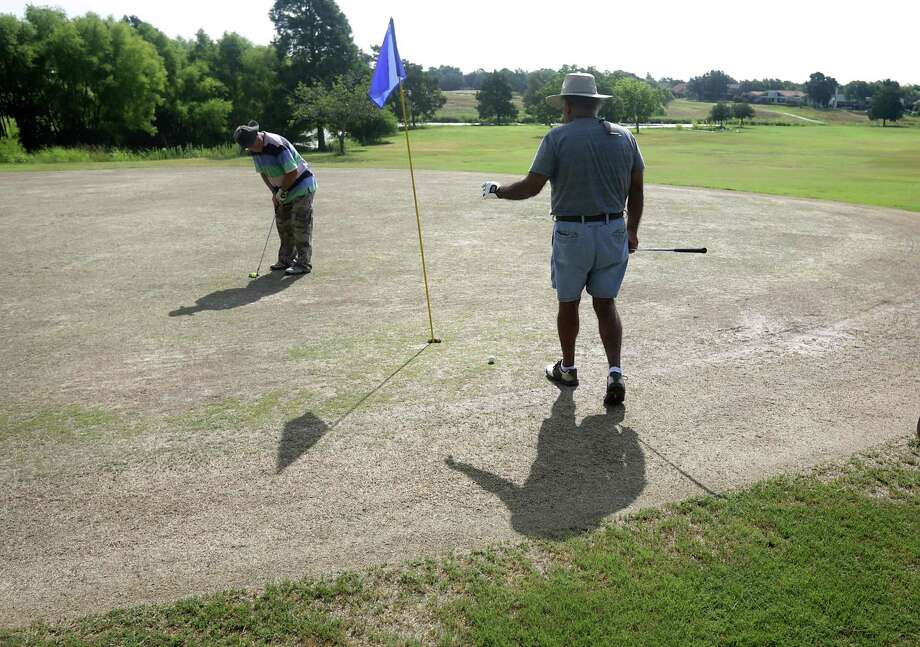 George Herbel putts near golfing buddy Dan Hernandez at Woodlake Golf Club last month. Two Woodlake creditors — the San Antonio River Authority and Nova Group — are weighing whether to foreclose on the property. Photo: San Antonio Express-News File Photo