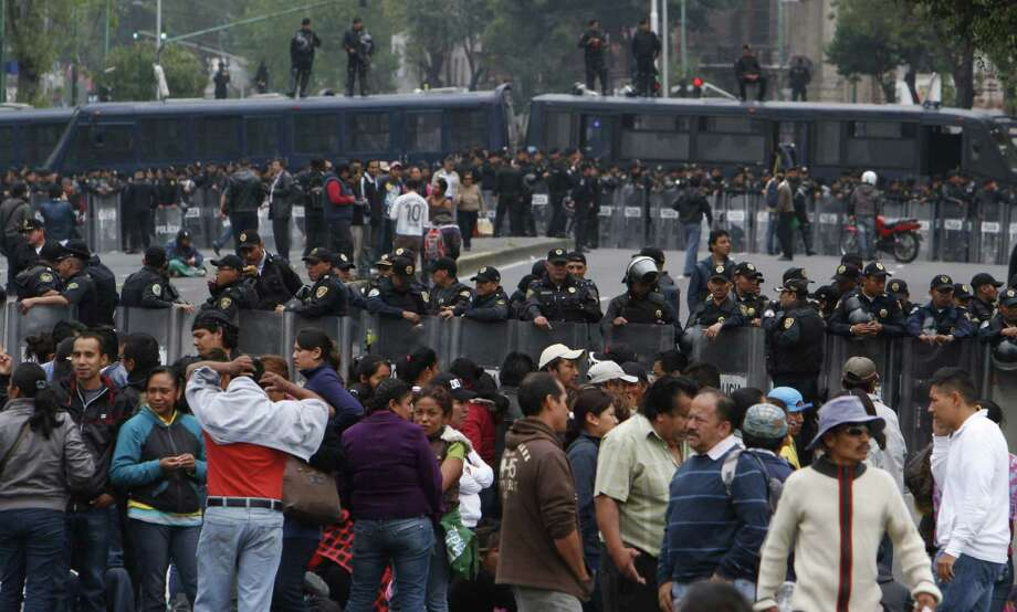 With police on guard, striking teachers block the Senate and downtown Mexico City on Tuesday. The Senate voted Wednesday to reform the country's public schools.