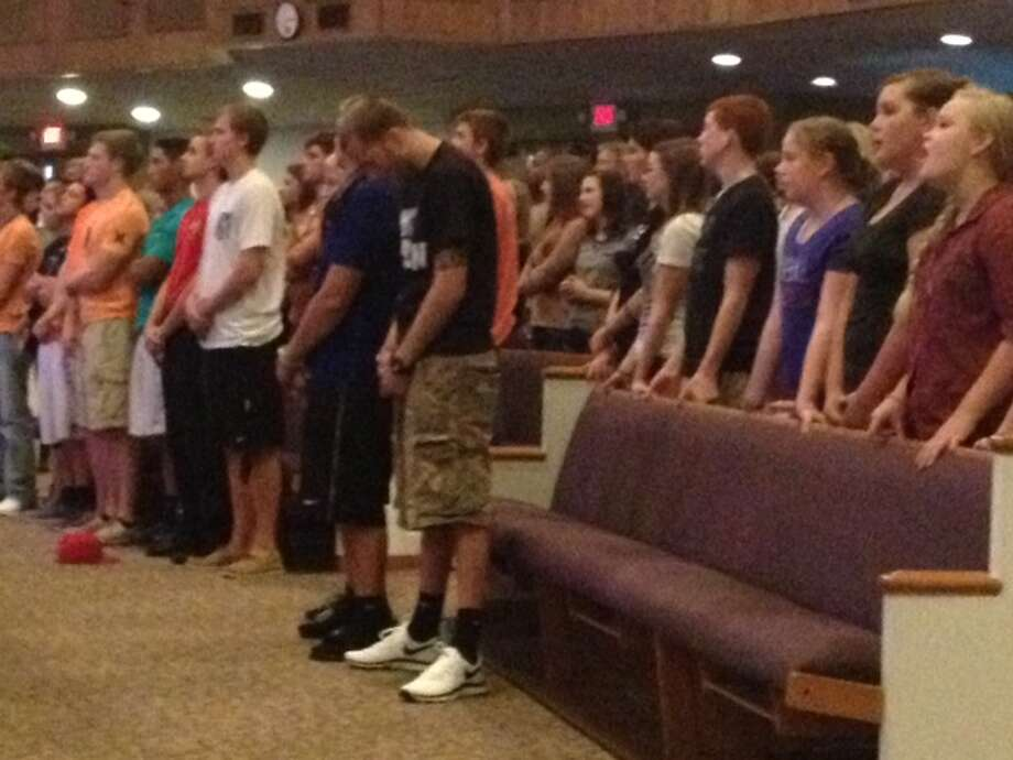 Worshippers pray for the school stabbing victims during a vigil at Spring Baptist Church on Wednesday evening.