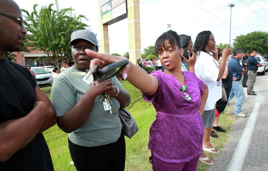 Parent Robin Fletcher points to an school entrance where she things the students will be released as parents wait for student dismissal across the street from Spring High School after a 17 year-old student was fatal stabbed during an altercation in the cafeteria on Wednesday, Sept. 4, 2013, in Spring. Photo: Mayra Beltran, Houston Chronicle / © 2013 Houston Chronicle