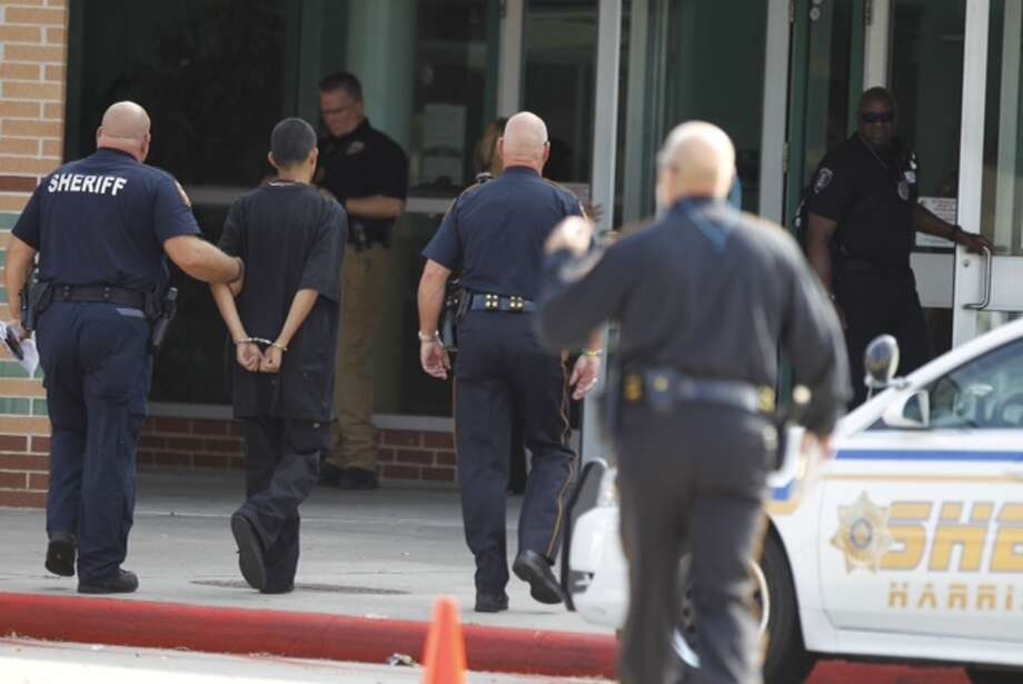 A man is walked into Spring High School in handcuffs as police investigate a stabbing incident on the morning of Wed., Sept. 4.  Photo: Brett Coomer, Chronicle