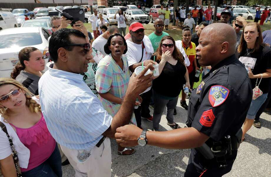 A law enforcement officer explains how parents can pickup their children outside Spring High School Wednesday, Sept. 4, 2013, in Spring, Texas, after 17-year-old student was stabbed to death and three others were injured after a fight at the Houston-area high school. Photo: AP