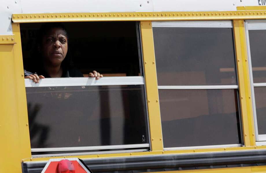 A woman looks out a school bus as it leaves Spring High School Wednesday, Sept. 4, 2013, in Spring, Texas. A 17-year-old student was stabbed to death and three others are injured after a fight at a Houston-area high school. (AP Photo/David J. Phillip) Photo: David J. Phillip, Associated Press / AP