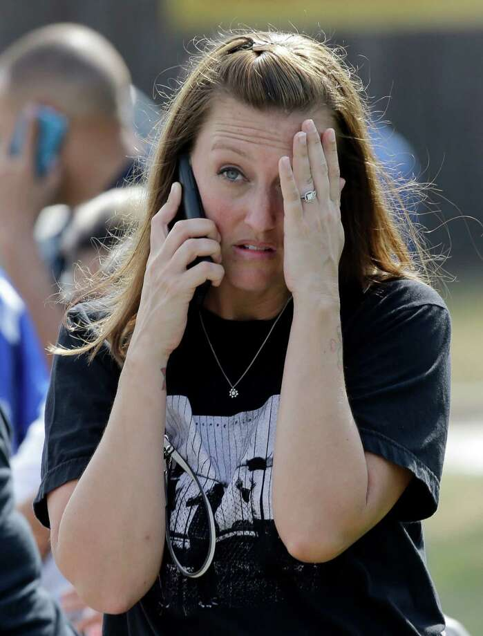 Laurie Garza talks on the phone as she waits for her daughter outside Spring High School Wednesday, Sept. 4, 2013, in Spring, Texas. At least one person has been killed and others injured in an altercation at the high school in suburban Houston.The Harris County Sheriff's Office did not say whether the people involved in the fight about 7 a.m. Wednesday at Spring High School were all students. Photo: AP