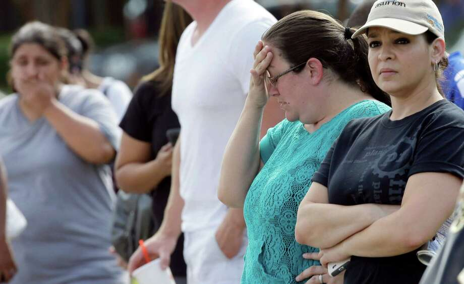 Carrie Estrada, right, and Mindy Weaver, second from right, wait for their children outside Spring High School Wednesday, Sept. 4, 2013, in Spring, Texas. At least one person has been killed and others injured in an altercation at the high school in suburban Houston. The Harris County Sheriff's Office did not say whether the people involved in the fight about 7 a.m. Wednesday at Spring High School were all students. Photo: AP