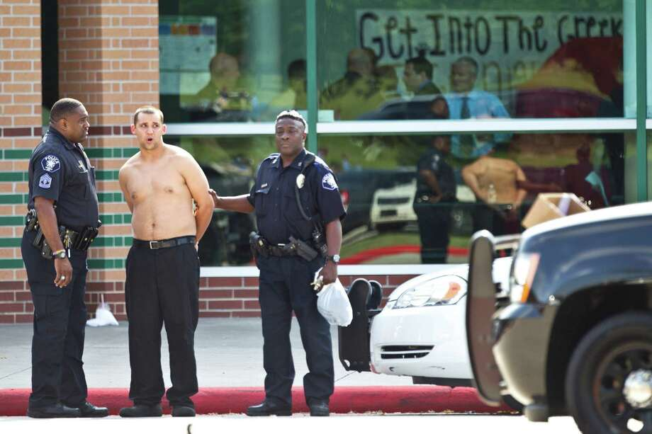 A man is led from the school in handcuffs following a stabbing incident at Spring High School Wednesday, Sept. 4, 2013, in Spring. A student was stabbed to death and three others are injured after a fight at suburban school. Photo: Brett Coomer, Houston Chronicle / © 2013 Houston Chronicle
