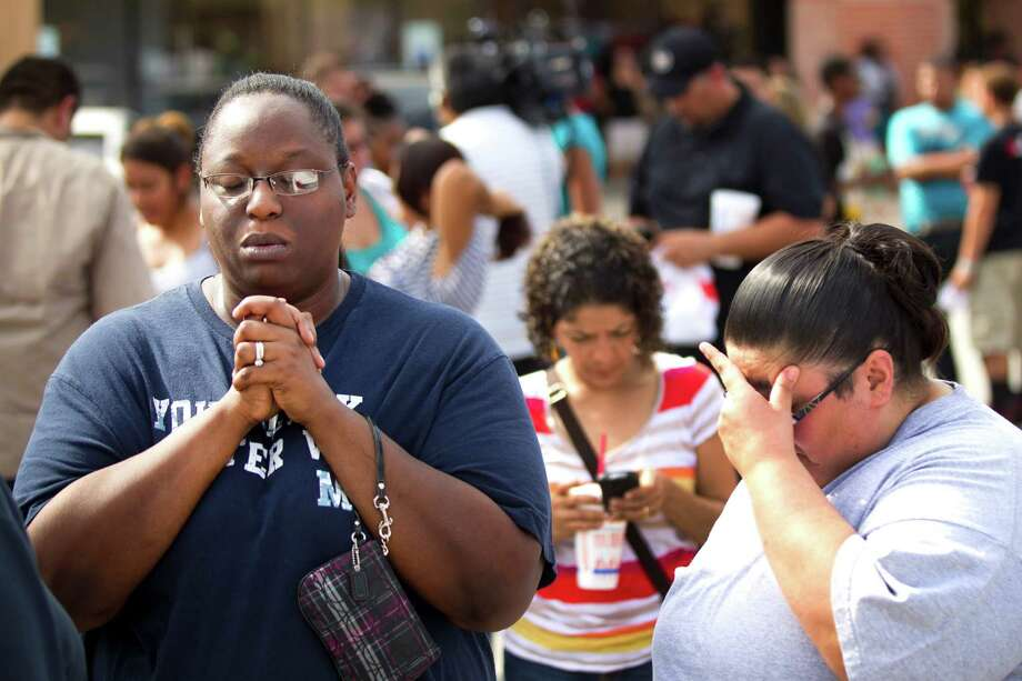 Nekita Smith, left, stands across the street from Spring High School following a stabbing incident at Spring High School Wednesday, Sept. 4, 2013, in Spring. A student was stabbed to death and three others are injured after a fight at suburban school. Smith was waiting of her son to be released from the school with the rest of the students. Photo: Brett Coomer, Houston Chronicle / © 2013 Houston Chronicle