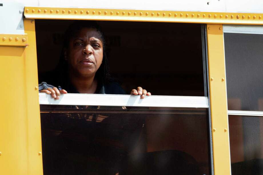 A woman looks out a school bus window following a stabbing incident at Spring High School Wednesday, Sept. 4, 2013, in Spring. A student was stabbed to death and three others are injured after a fight at suburban school. Photo: Brett Coomer, Houston Chronicle / © 2013 Houston Chronicle