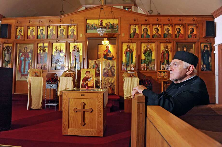 Fr. Gregory DesMarias sits in a pew at St. George Antiochian Orthodox church Tuesday afternoon, Sept. 3, 2013, in Albany, N.Y. The church was built 80 years ago by Syrian immigrants who settled in city's South End. (Lori Van Buren / Times Union) Photo: Lori Van Buren / 00023722A