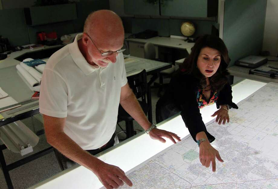 Bob Abbott, vice president at Key Maps, and Jen Marie Rau, owner, look over a special map project. Wall maps help keep the company afloat, plus genuine affection that many people have for holding and actually reading maps rather than staring at a  device's screen. Photo: Mayra Beltran, Staff / © 2013 Houston Chronicle